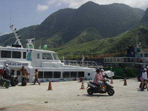 view of ferry on Orchid Island, Taiwan with mountains in the background.